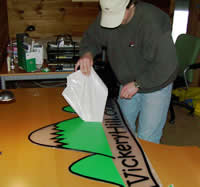 dave houle applies the vinyl to the smartbeetle vickeryhill.com sign
